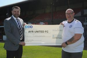 Jamie presents a cheque to vice-chairman Davie Smith.